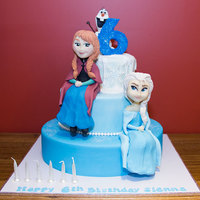 "Elsa And Anna... And Olaf Cake 12"" and 9"" Red velvet cake with milk chocolate ganache and fondant.6"" Styrofoam dummy.Gumpaste Olaf, Anna and Elsa"