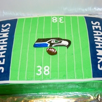 "Seattle Seahawks Cake 1/4 sheet vanilla pudding w/raspberry-vanilla icing. Fondant accents, logo is hand drawn on edible fondant paper. The ""yardline""..."
