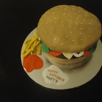 Hamburger Three layers of chocolate cake. The buns and humburger toppings are in fondant; the burger patty is chocolate buttercream on a thin layer...