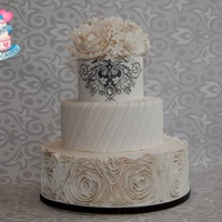Rosette Ruffle Bottom Knife Pleats On Second Tier And Royal Icing Stencil On Top Tier With Hand Made Gumpaste Peony Roses And Stephanotis Rosette ruffle bottom, knife pleats on second tier and royal icing stencil on top tier with hand made gumpaste peony, roses and stephanotis...