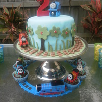 Thomas The Tank Engine Cake And Cupcake Train  Fondant accents, trains on cake and carriage of cupcake train are toys, the cupcake toppers are handmade out of fondant. My third ever...