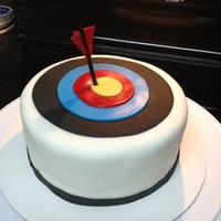 Archery Target Cake  8 inch round double layer funfetti with vanilla buttercream covered in MMF. Archery arrow is a wooden dowel painted in black food coloring...