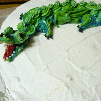 Dragon Cake dragon had flames from sparkle candle coming from mouth had candy eggs around it.