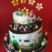 Super Mario Birthday My sons birthday cake! Iced in buttercream and all decorations, including the mushrooms and bananas are made with fondant except the...