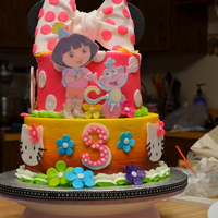 Dora, Hello Kitty, And Minnie Mouse Cake Two tier 8 in. strawberry cake and 6 in. white almond cake with buttercream icing, fondant accents and icing plaque Dora characters.
