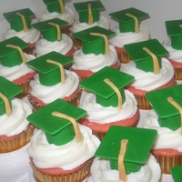 Graduation Cupcakes Strawberry cupcakes with buttercream icing, topped with homemade fondant graduation cap.