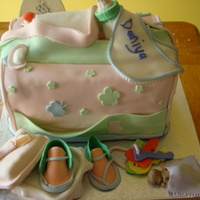 Large Diaper Bag Cake W/accessories This one has the works - gift shoes, bib, pacifier, teether, diaper, bottle. I need a new technique for making the bottle...