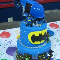 Batman Tiered Cake This is a copy of a design by MyDelight Cupcakery, requested by client. Batman symbol and city buildings are homemade chocolate MMF, the...