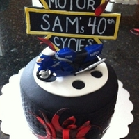 Mototcycle Tire cake covered in fondant with gumpaste sign and toy
