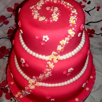 Blossom Swirl 3 tier cake covered in pink sugarpaste, decorated with a blossom swirl, various blossom patterns and sugarpaste beads