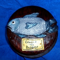 "'caught The Bugger' Fish Sugarpaste fish on a cake base fashioned to look like a wooden plaque and gold sign with message ""Caught the Bugger"""