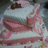 Pretty In Pink Vanilla Cake covered with Butter Cream Icing and Fondant. All details are edible. The baby is made out of Tootsie Rolls