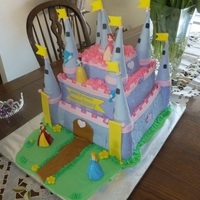 Disney Princess Castle Three tiered chocolate cake with vanilla frosting and vanilla pudding. All objects on cake are edible.
