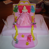 Princess Aurora Girl cake with porcelain princess and accesories covered in fondant.