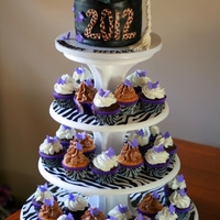 "Graduation Cupcake Tower Chocolate and chocolate chip cupcakes with a 6"" cake on top in the shape of a graduation cap."