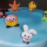 Moshi Monsters   vanilla sponge cake with multicoloured buttercream filling covered in blue fondant. moshi monsters figures made from gumpaste