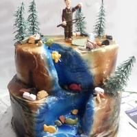 Gone Fishing carved cake in buttercream with candy rocks and fisherman figuring