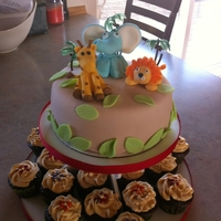 Jungle Shower Fondant covered cake, with fondant animals. Cupcakes are frosted with buttercream and embilished with chocolate covered sunflowerseeds for...
