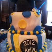 Graduation tiered cake covered in fondant, topped with hat and diploma