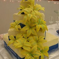 Yellow Stargazer Lilies This four-tiered, square wedding cake displays 15 hand-made yellow stargazer lilies. A blue fondant ribbon completes the bride's...