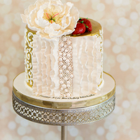 Ruffles And Pearls Gilded birthday elegance in ruffles and pearls topped with a white peony and strawberries.