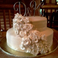 Ivory Cake W/ White Roses W/ Gold Painted Tips 2 tier Ivory cake with white roses with painted gold tips, and gold sparkly ribbon!