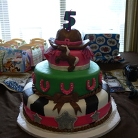 Cow Girl Cake 3 tier cowgirl cake cow design is chocolate, green is lemon and the top tier is strawberry all covered in fondant. Cowgirl hat is a shaped...