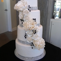 White Peony And Rose Cake Lemon blueberry four tier cake with white peonies and roses accented with navy blue berries for the wedding colours and lots of sparkles....