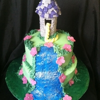 Tangled Birthday Cake made of vanilla cake and buttercream with fondant accents and piping gel and edible glitter added to blue icing for the water. The tower...