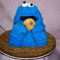 "Cookie Monster Made for a friends daughter. Head and hands are Rice Krispy and body is cake sitting on a 16"" round chocolate chip cookie base."