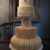 4 Tier Victorian Influence Wedding Cake In Ivory With Ruching And Lace Accents 4-tier Victorian influence Wedding cake in Ivory with ruching and lace accents.