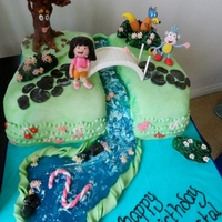 Dora The Explorer Dora the explorer, the left half of this cake is strawberry and the right half is chocolate, details are gumpaste & fondant, tree...