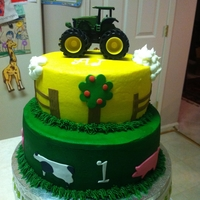 John Deere Farm Animal Cake bottom tier is chocolate fudge. top tier is strawberry cream. BC with fondant and gumpaste accents. Tractor is keepsake toy for birthday...
