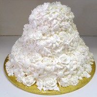 Floral Garden This is a three tiered blush iced cake. It is covered with all different white flowers and leaves.