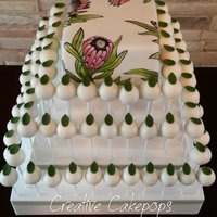 Hand Painted Protea Wedding Cake And Cake Pops Art Nouveau themed wedding cake and cake pops with handpainted Protea flowers and cake pops with leaf detail.