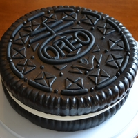 "Oreo! Two 10"" dark chocolate cakes covered in black fondant. Details are black fondant cutouts. In between the cakes is a layer of..."