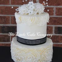 White And Black Wedding Cake   both tiers iced with buttercream and piped buttercream ruffles