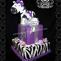 "Zebra Baby Shower Cake  10"" square bottom tier with MMF zebra print6"" cube top tier in purple MMF with silver fondant bowCrown, pacifier and rattle are..."