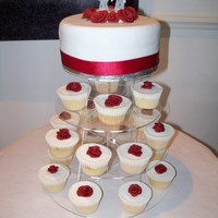 First Wedding Cake  The bride asked for a simple chocolate cake, iced in white with a red ribbon and roses, and plain sponge cupcakes decorated to match. She...
