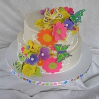Whimsical Flowers And Butterflies Red Velvet cake covered and filled with cream cheese frosting. Fondant and gumpaste flowers and butterflies