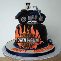Motorcycle Birthday Cake 6 inch round cake covered in black chocolate fondant to look like a tire. Fondant motorcycle on top. Owen's last name is intentionally...