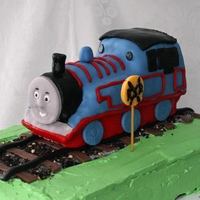 Thomas The Train Chocolate almond cake covered and filled with buttercream frosting. Thomas is RKT covered in MMF.