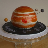 Jupiter With Moons Red Velvet cake filled with cream cheese frosting and covered in MMF. Hand painted to look like Jupiter. The four moons are fondant.
