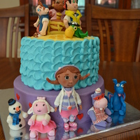 Jake & The Neverland Pirates And Doc Mcstuffins The top tier is a rainbow cake (on the inside) and frosted in buttercream. All the characters on the cake are fondant. The bottom tier is...