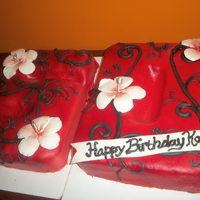 50Th Black And Red Birthday Cake Carved 2 11x15 pans. Covered in MMF and the swirls were done in royal icing. Flowers are gumpaste.