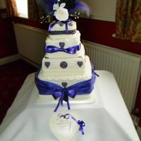 4 Tier Sponge Wedding Cake Chocolate Lemon And Orange Tiers Covered In White Sugar Paste With White And Purple Sugar Paste Decorations *4 tier sponge wedding cake, Chocolate, lemon and orange tiers. Covered in white sugar paste with white and purple sugar paste decorations...