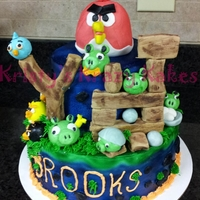 Angry Birds Cake 2 tier cake iced in butter cream with hand made fondant and gum paste birds, pigs, eggs, sling shot, boards and rocks.