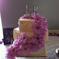 Kaylee Wedding Cake Ivory fondant with real purple flowers cascading down front