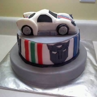 Transformer Cake Covered using MMF. First time to carve a car! Old-school 'Jazz.' Autobot and Decepticon emblems around the sides 'bout made...