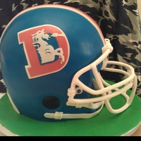 "Throwback Bronco Helmet Cake Two 9"" cakes, carved, gumpaste face guard."